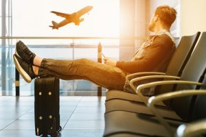 An image of a man with his suitcase and an aeroplane